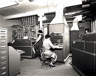Two technicians work at a large computer